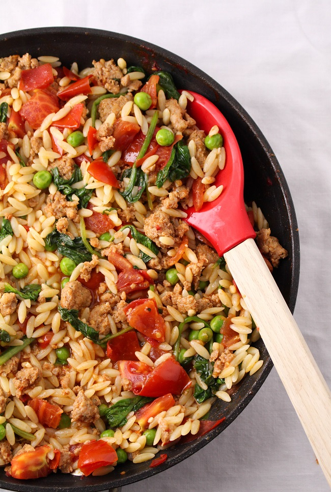 Orzo with sausage, tomatoes, spinach, and peas
