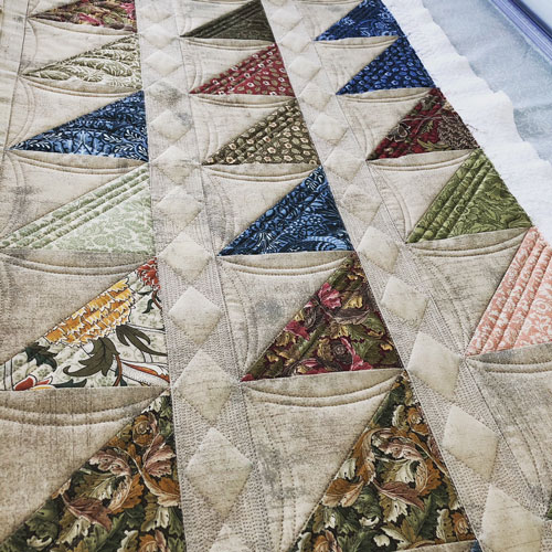 Half square triangle quilt with free motion quilted diamond sashing