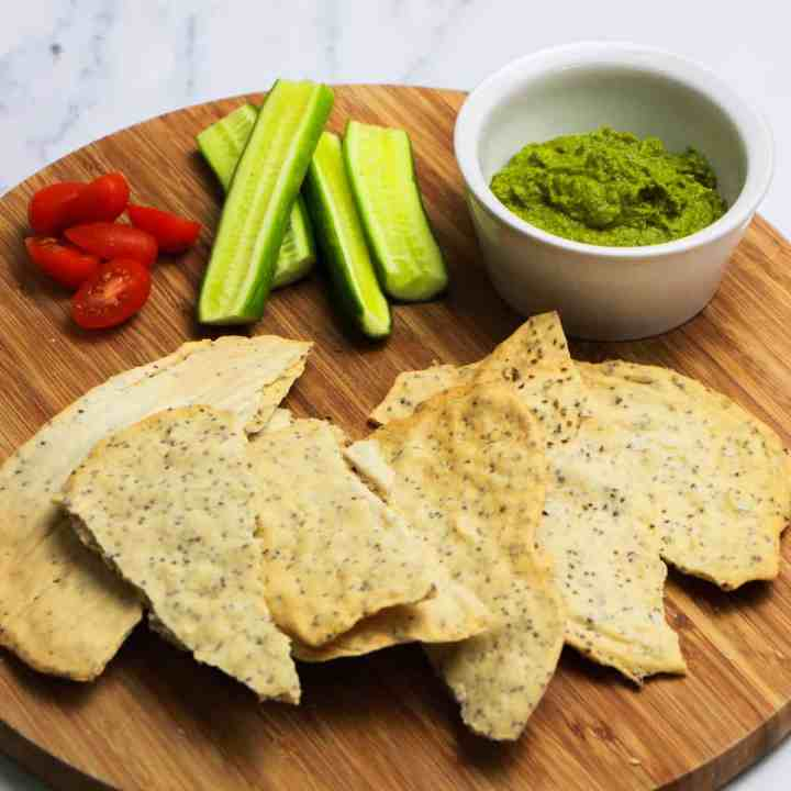 Photo of a pile of almond and chia crackers on a wooden chopping board with some cucumber, tomatoes and zingy green olive tapenade.