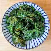 photo of a blue and white stripy bowl filled with crispy kale, on a wooden surface.
