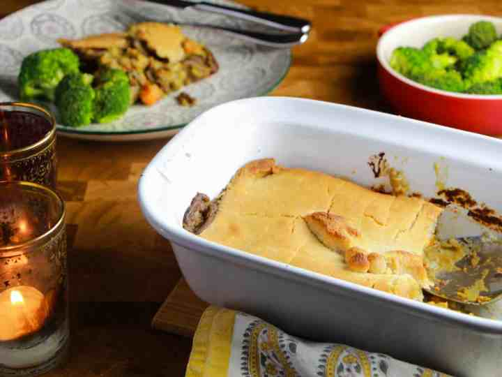 Photo showing Creamy Vegan Pot Pie in an oven dish with a portioned on a plate in the background and a bowl of broccli