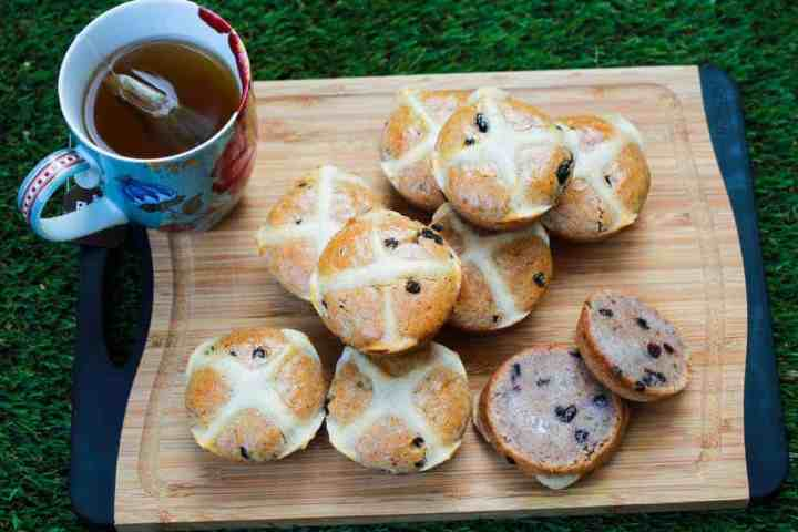 photo of hot cross buns piled on a chopping board with a cup of tea all on grass.