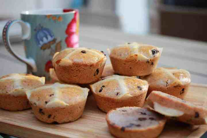vegan gluten-free hot cross buns piled onto a chopping board with a cup of tea behind.