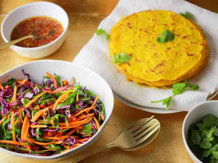 tray of the ingredients for the rainbow salad vietnamese pancakes - bowl of colourful salad in the foreground and a plate with a pile of pancakes in the background plus a bowl of spicy dressing and a bowl of coriander.