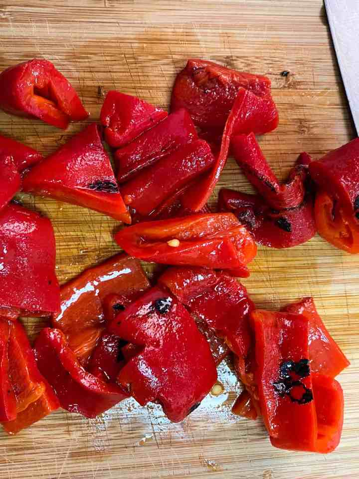 photo of roasted red peppers being chopped on a board.