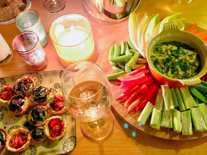 A candlelit table spread with canapés including vegan and gluten-free tartlets and crudités and dip