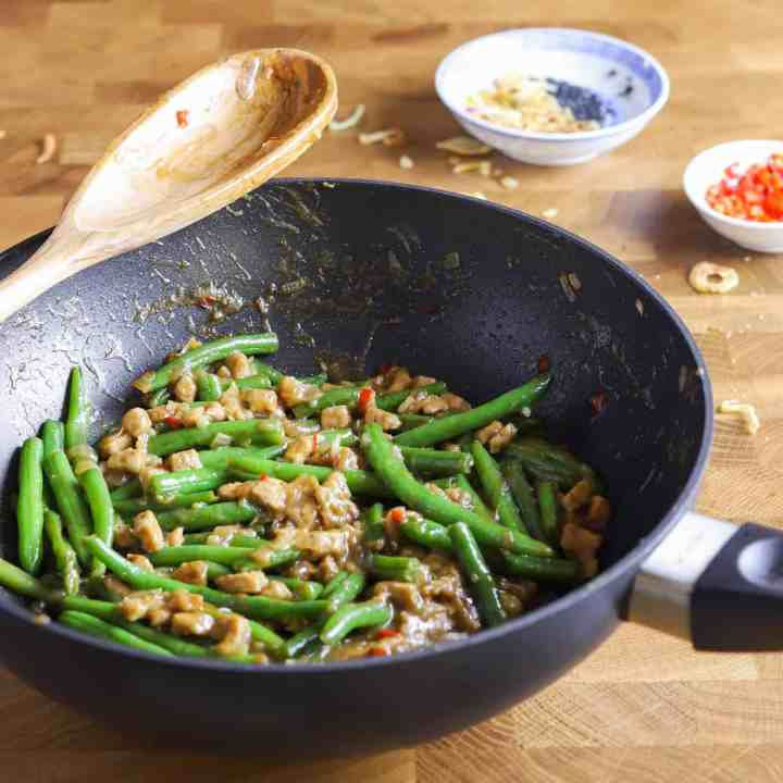 photo of a wok containing vegan chinese green beans and tempeh recipe on a butcher block surface