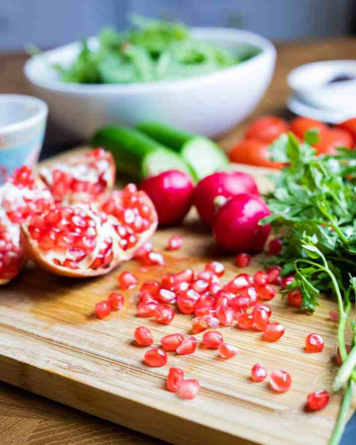 Photo of a chopping board with cut pomegranate and the seeds plus radishes, cucumbers, parsley and a bowl of rocket int he background.
