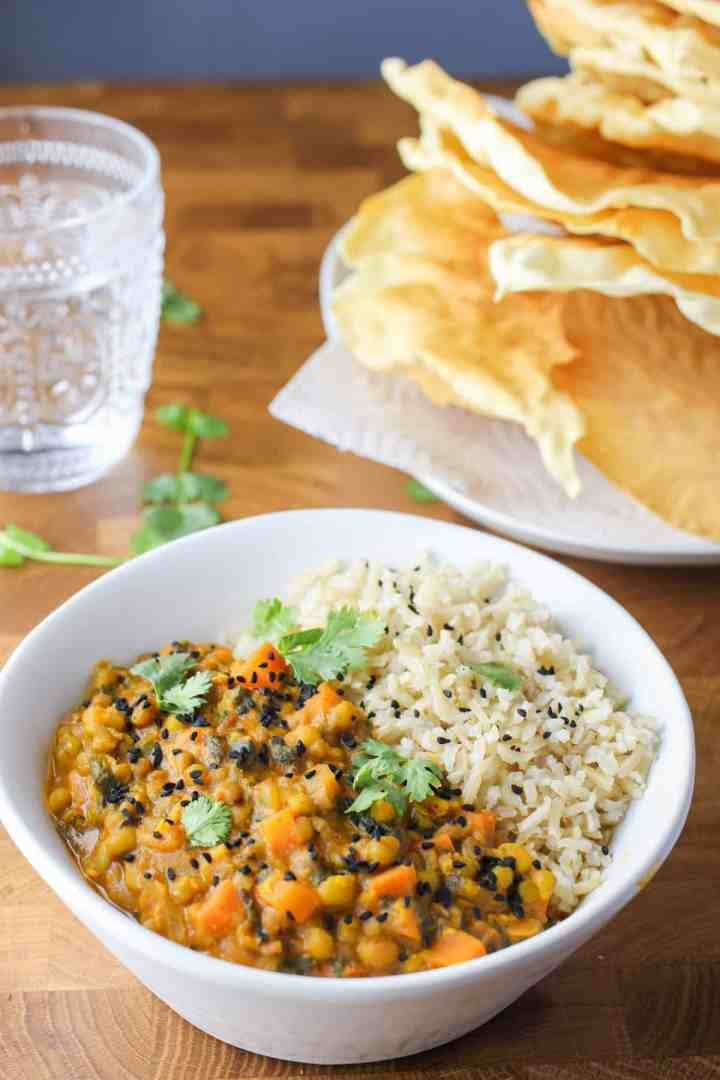 Photo showing a white bowl with Mung Bean Curry and brown rice, all set on a wooden table with a plate of poppadoms in the background and a glass of water and some coriander leaves sprinkled around.