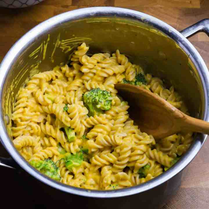 a big pan filled with twirly pasta mixed with healthy vegan cheese sauce and broccoli, all on a wooden tabletop.