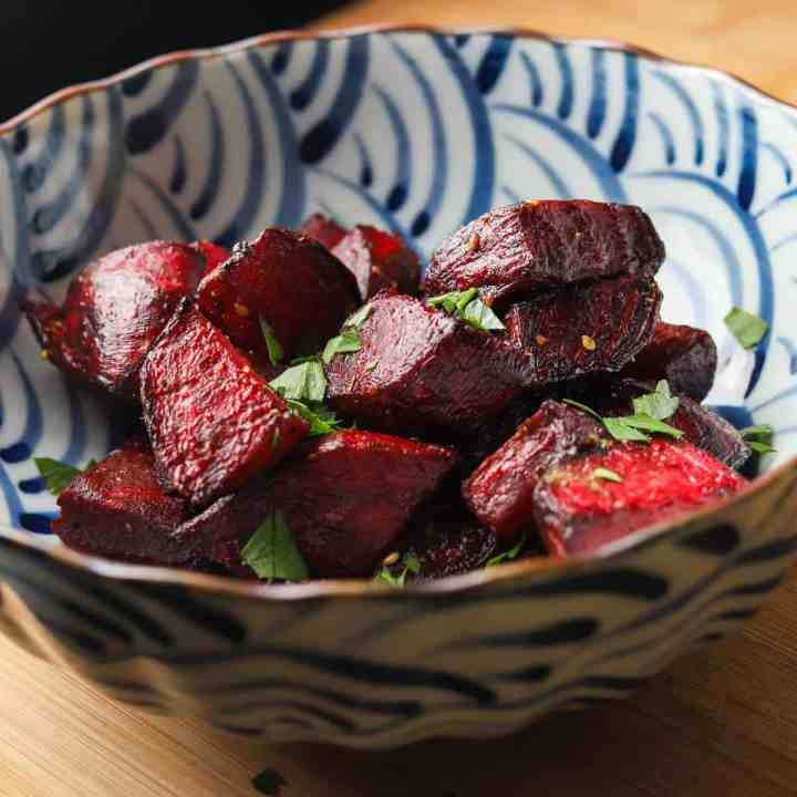 Photo of a blue and white bowl filled with roast beetroot cubes and some chopped parsley sprinkled on top.