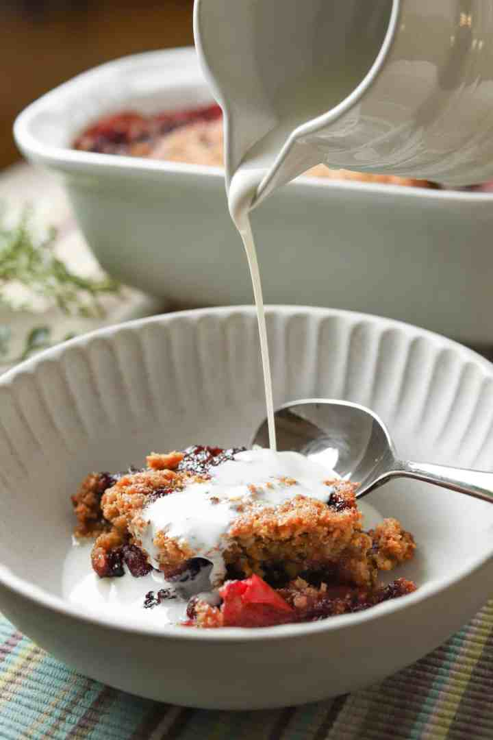 photo of a bowl with a portion of blackberry & apple crumble and vegan cream being poured from a jug.