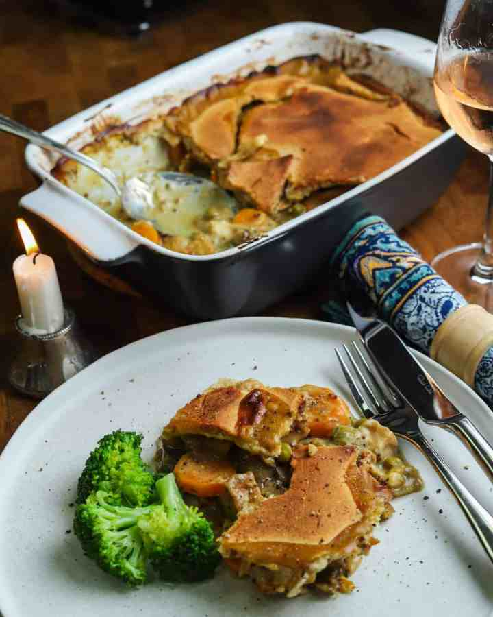 Photo of a plate of vegan pot pie with broccoli and the serving dish in the background and a candle, glass of wine and napkin.