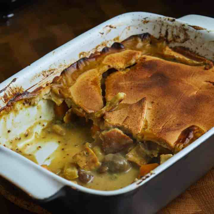 Photo of a casserole dish half served, with some filling spilling out from under the pastry.