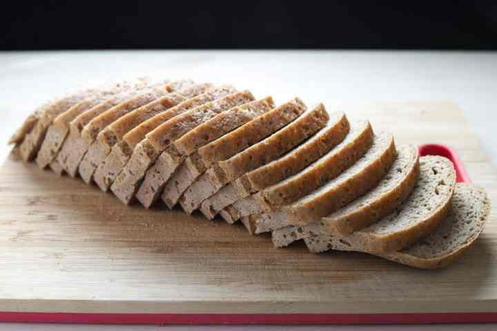 Photo of a sliced loaf of vegan gluten free bread on a bread board.