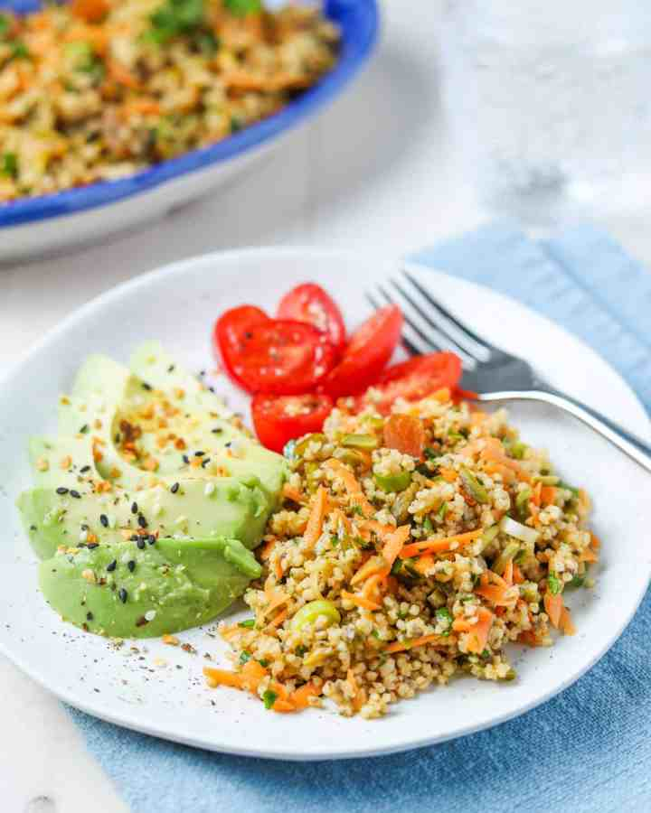photo of a plate of spiced millet salad with sliced avocado and cherry tomatoes, with a blue napkin, cutlery and bowl of millet salad in the background.