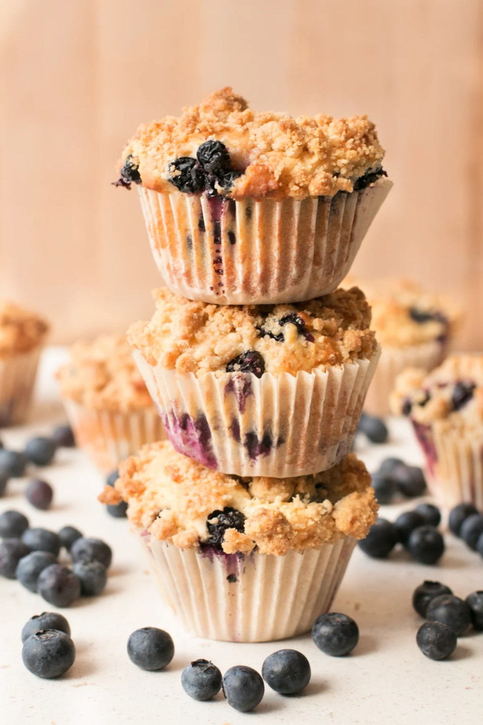 A stack of blueberry crumb muffins sitting on a white surface and surrounded by loose blueberries