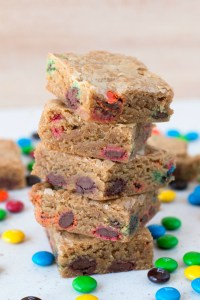 A stack of brown butter blondies with m&m's sitting on a white surface surrounded by loose m&ms