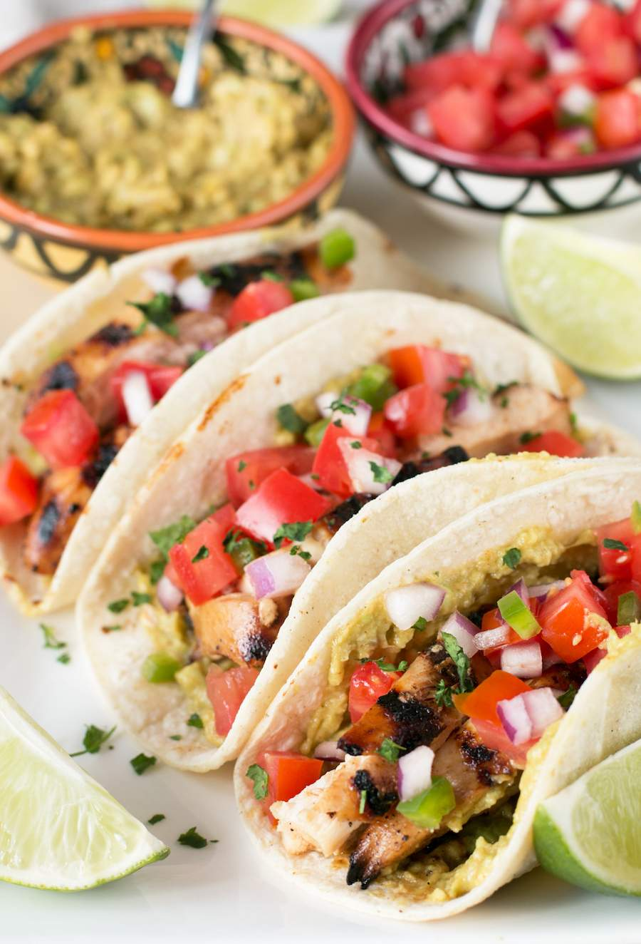 Three Mexican Chicken Tacos on a white plate in corn tortillas.