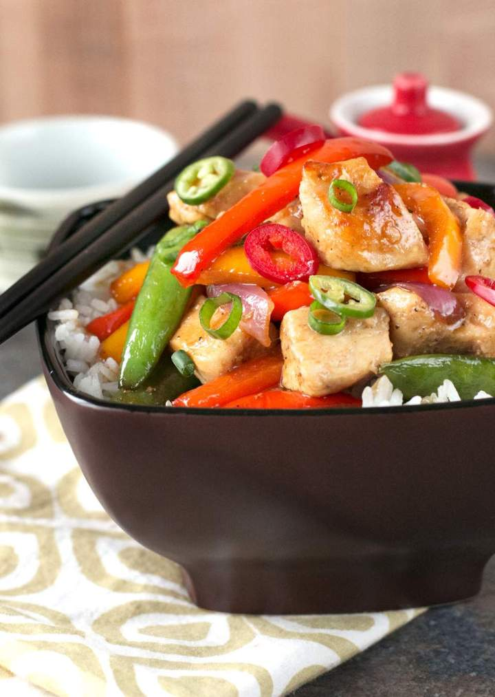 Sweet and Spicy Chicken Stir-Fry in a black bowl on a white and brown napkin with black chopsticks.