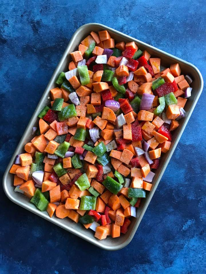 Sweet Potatoes, peppers, and onions on a baking sheet