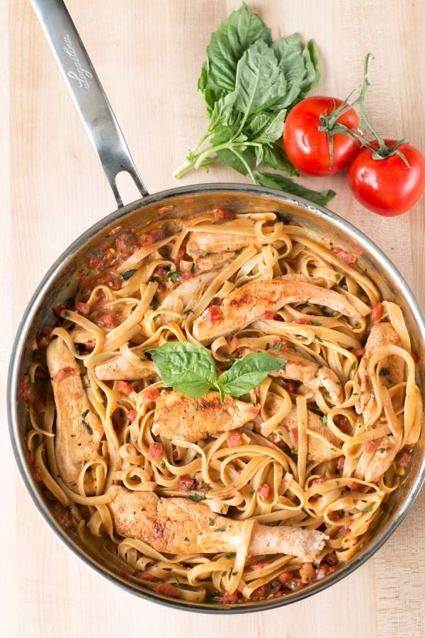 Tomato Basil Chicken Pasta recipe in a skillet with tomatoes and basil in the right corner