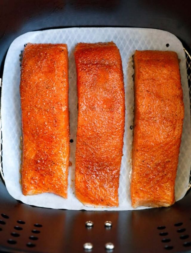 Raw salmon fillets in an air fryer.