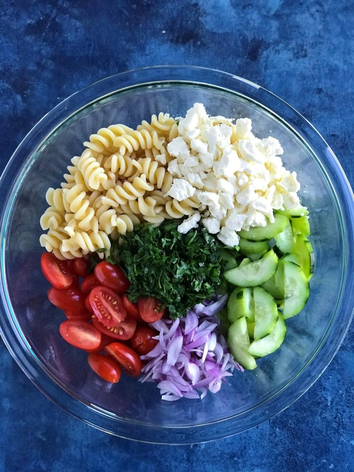Greek Pasta Salad ingredients - feta cheese, pasta, cucumbers, tomatoes, onion, and fresh parsley