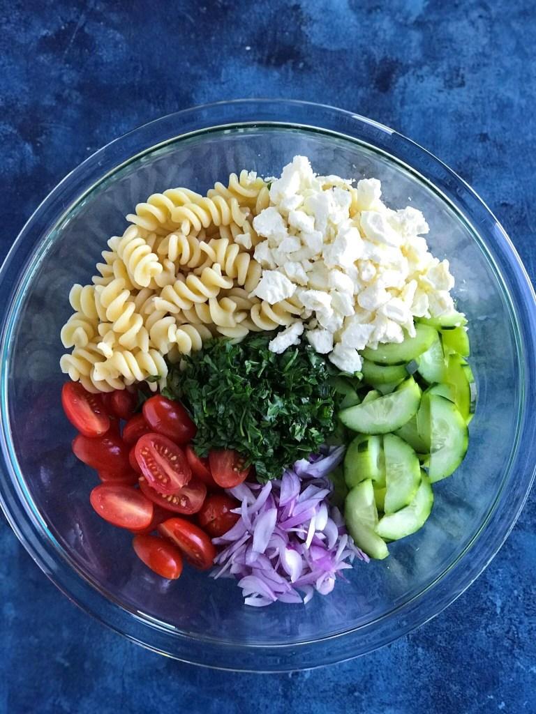 Greek Pasta Salad ingredients - feta cheese, pasta, cucumbers, tomatoes, onion, and fresh parsley