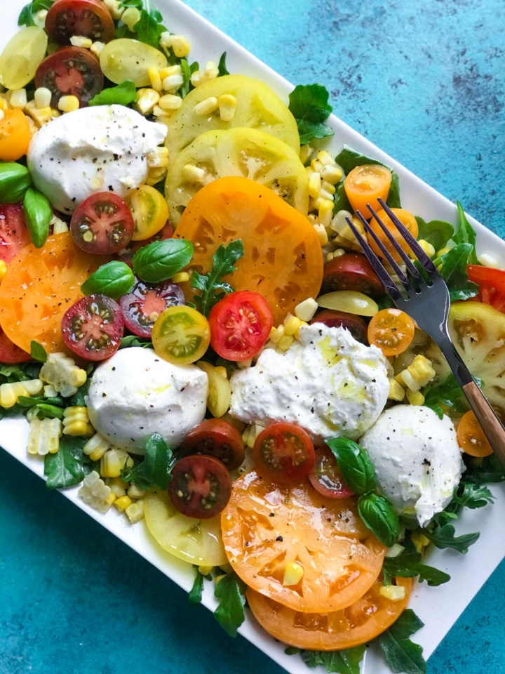 close up of tomatoes and burrata on a plate