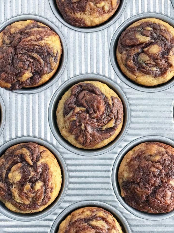 Nutella Swirl Banana Muffins in a muffin pan.