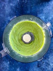 Blender with creamy avocado dressing smoothly blended inside on a blue counter.