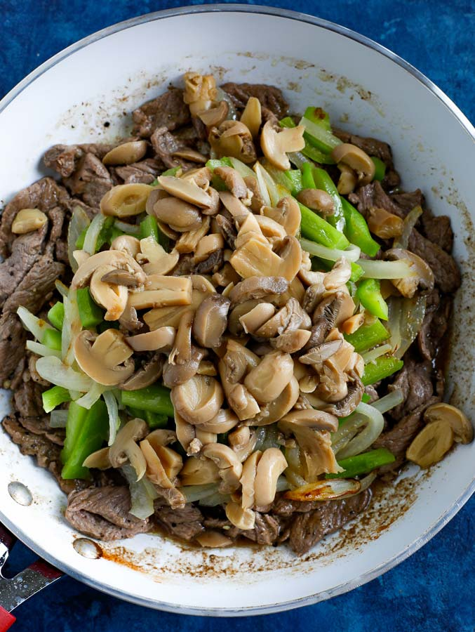 Steak, peppers, onions, and mushrooms cooking in a non-stick skillet on a blue counter.