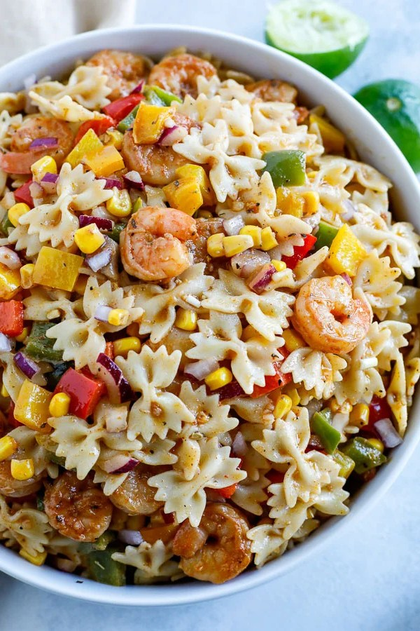 A large white bowl of shrimp fajita pasta salad and two limes in the background.