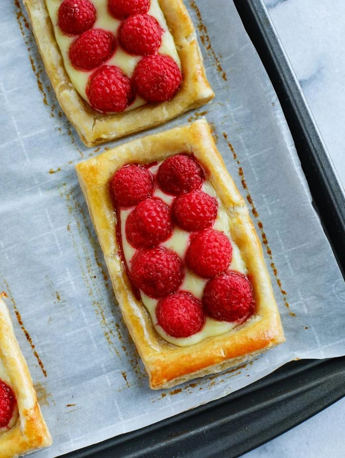 A close up shot of baked raspberry puff pastry rectangles on a parchment paper lined baking sheet.