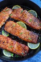 Four spicy honey garlic salmon pieces with lime wedges in a cast ion skillet.
