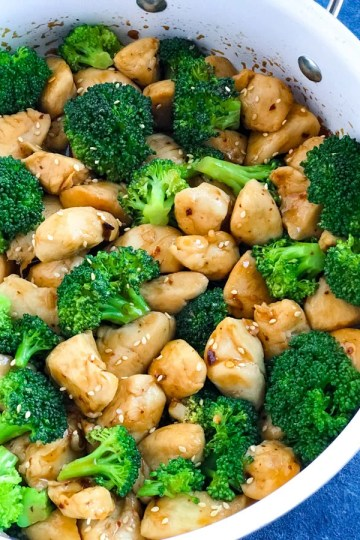 Spicy Teriyaki Chicken with Broccoli in a white skillet on a blue counter.