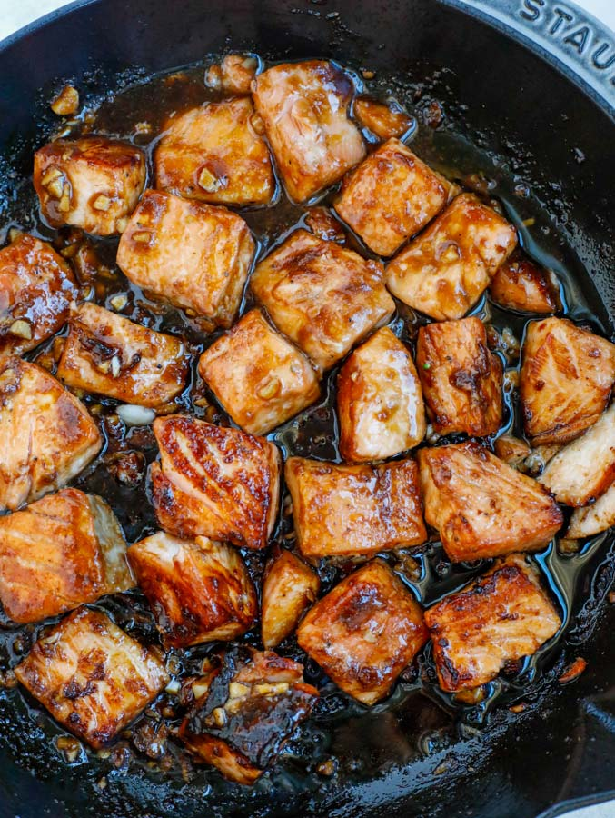 Salmon and teriyaki sauce cooking in a nonstick skillet.