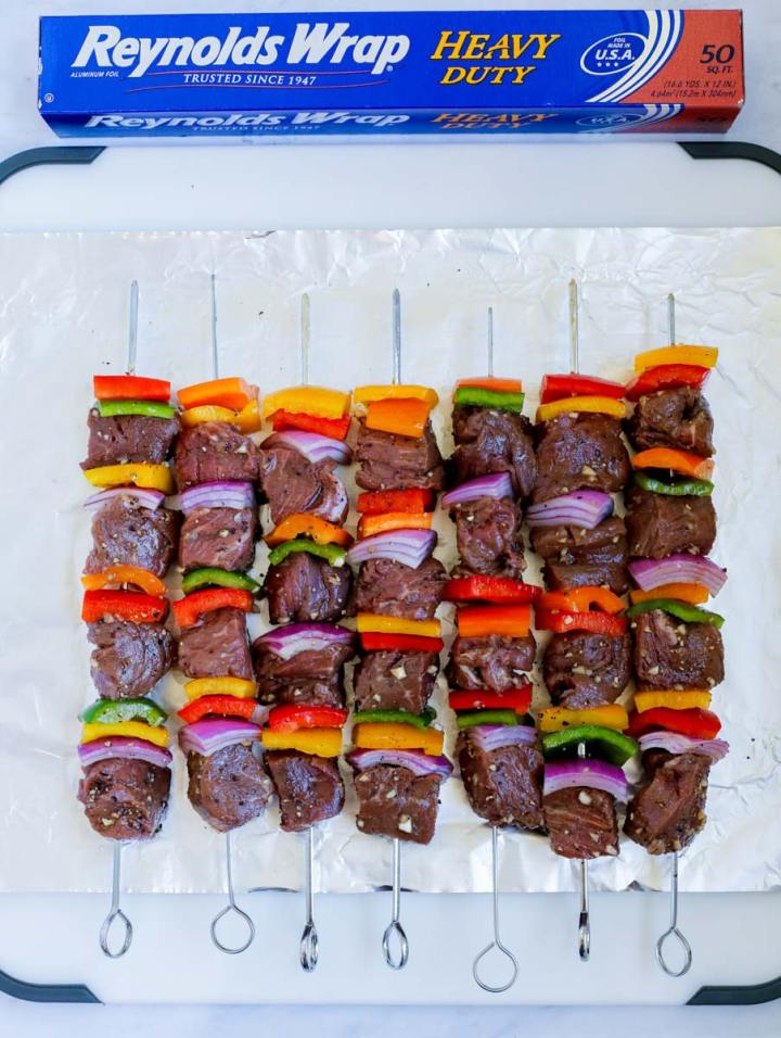 The beef kebobs before grilling laid on foil