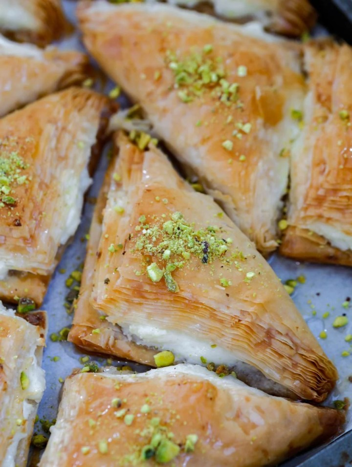 baked shaabiyet in a tray garnished with pistachio