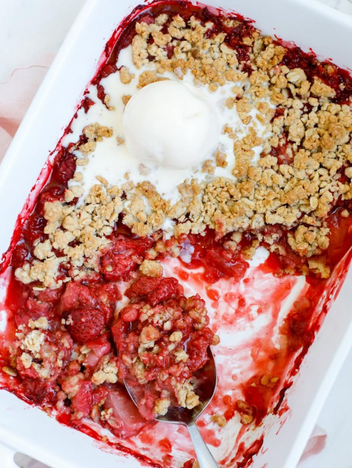 strawberry crisp in a baking dish, with a spoon and a scoop of vanilla ice cream