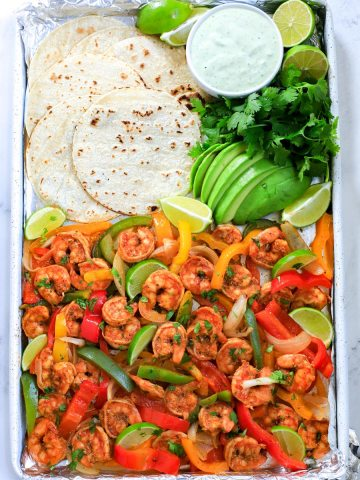shrimp fajita in a sheet pan with tortilla, avocado and dressing