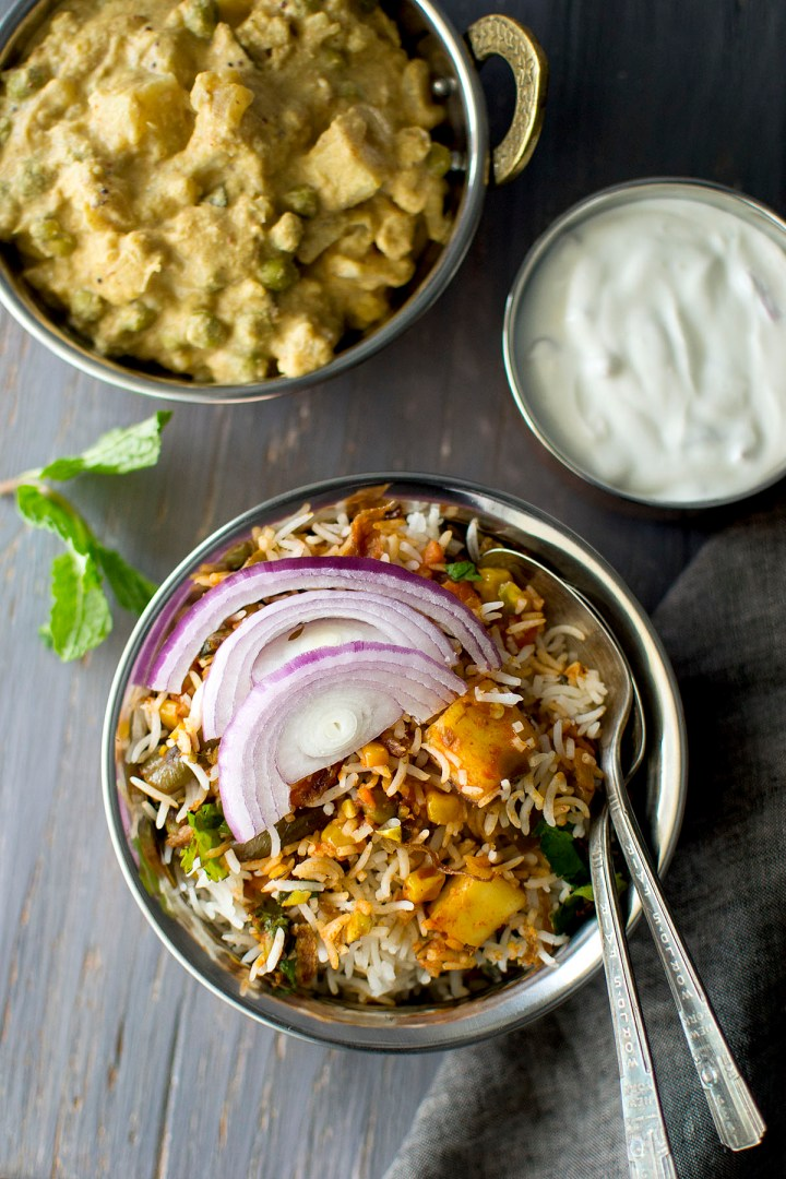 Steel bowl with rice topped with sliced onion and yogurt, curry in the background