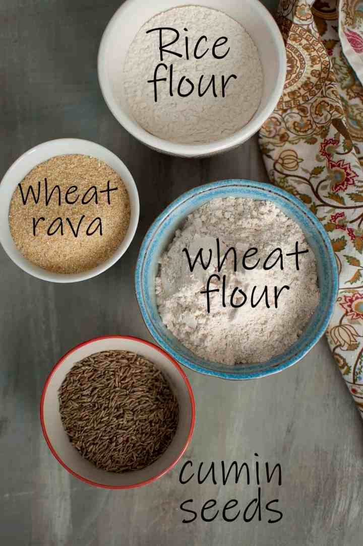 Bowls with Ingredients for the recipe - rice flour, wheat rava, wheat flour, cumin seeds