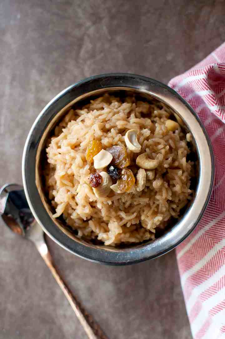 Steel bowl with rice pudding topped with cashews and raisins