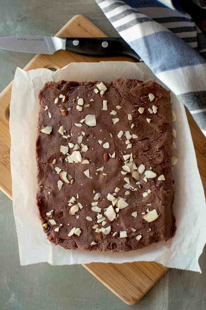 Chopping board with parchment paper with cooked fudge