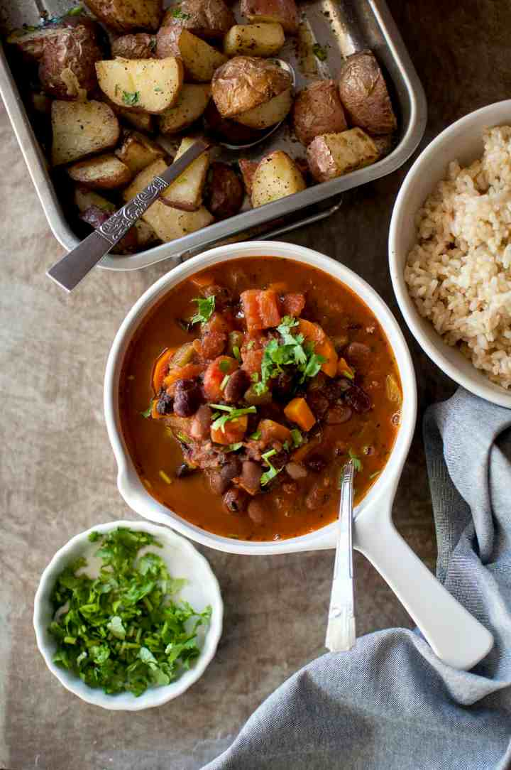White bowl with Vegetarian 3 Bean Stew, steel baking pan with roasted potatoes and brown rice