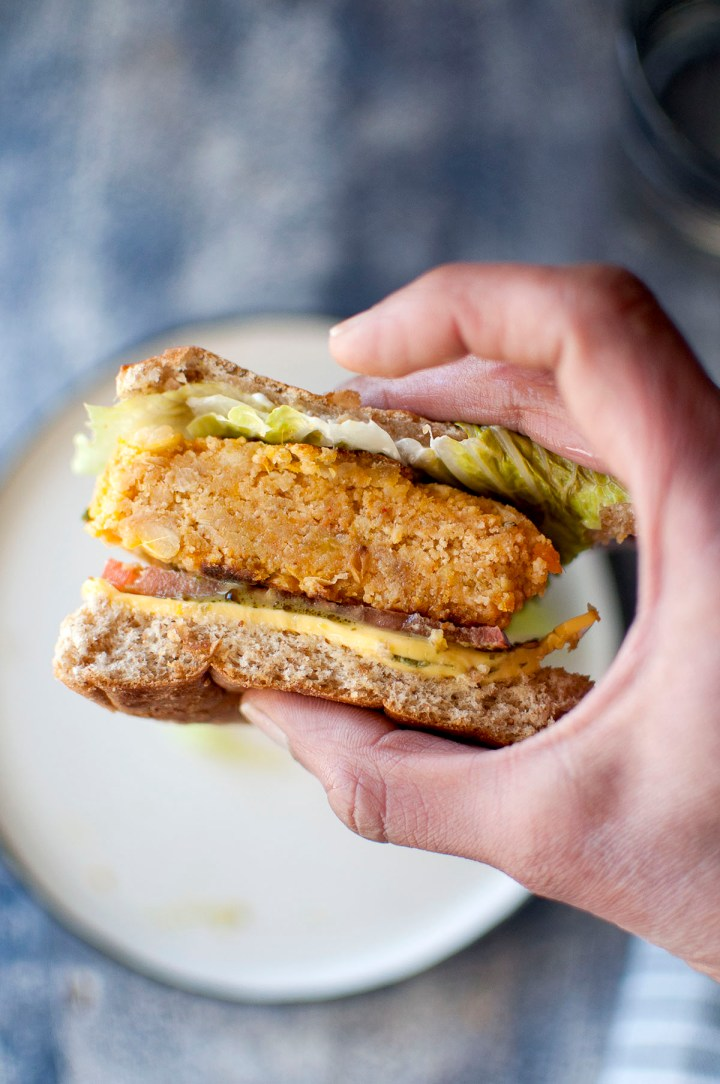 Hand holding a burger sandwich with veggie patty, cheese slice, lettuce and tomato slice