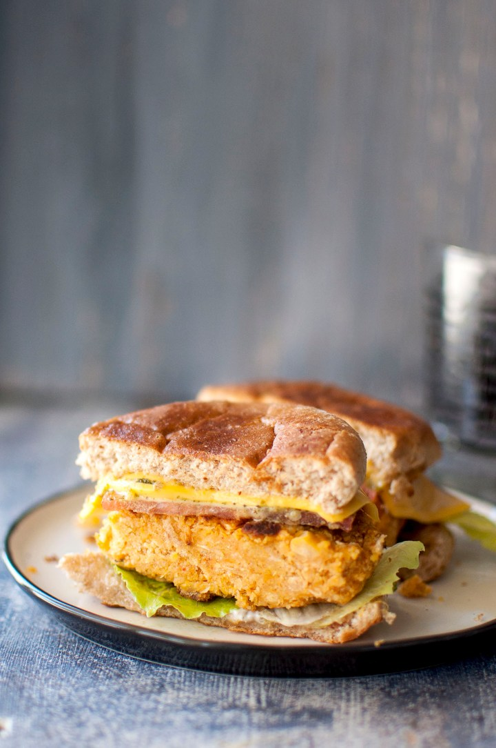 White plate with halved sweet potato chickpea burger sandwich