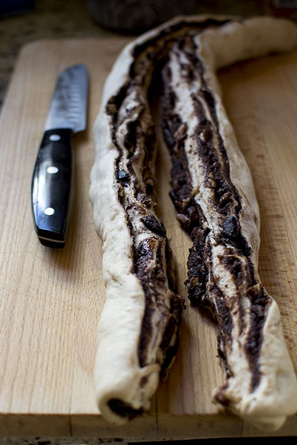 """Starting at one of of the long ends, roll up the dough tightly to make a 20"""" log."""
